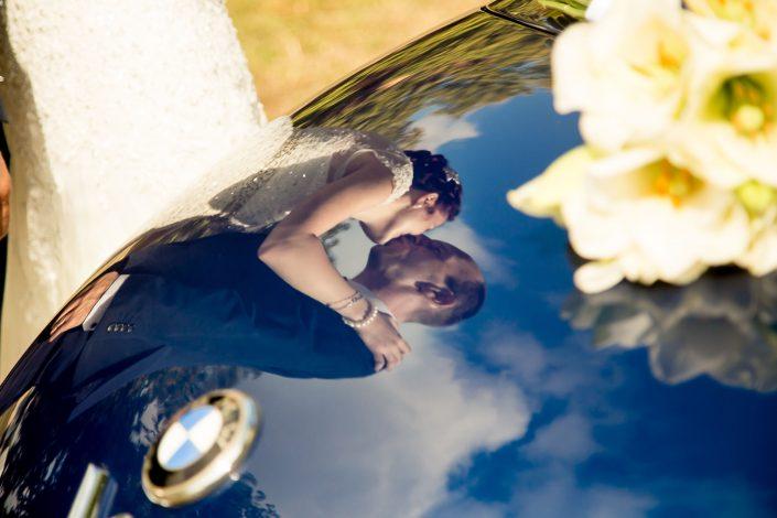 Brautpaar spiegelt sich im Kofferraum des HochzeitsAutos