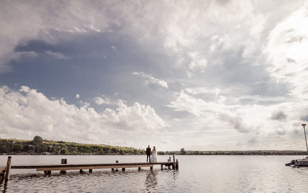 Weitwinkelaufnahme Brautpaar steht auf einem Steg und schaut in die Zukunft © Andreas Pöcking Fotograf Erfurt