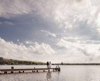 Weitwinkelaufnahme Brautpaar steht auf einem Steg und schaut in die Zukunft