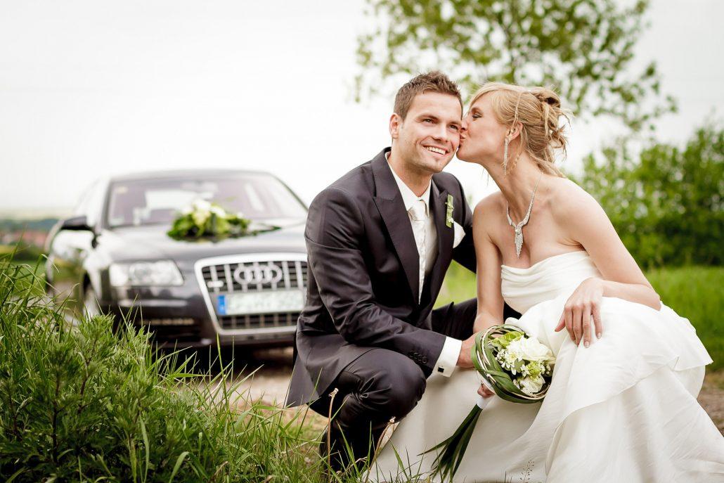 Brautpaar im Gras mit Hochzeitsauto im Hintergrund