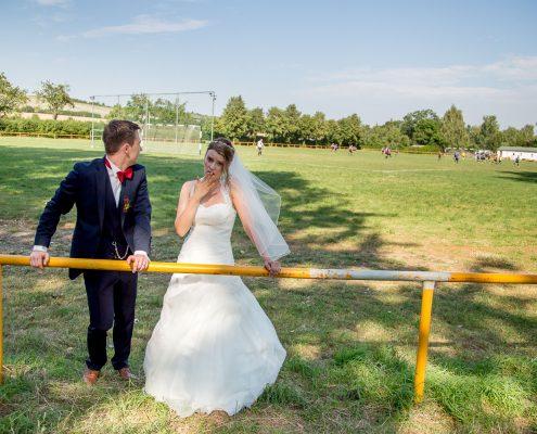 Hochzeitspaar am Fußballfeld, er schaut zum spiel, sie gelangweilt in die Kamera ,-)