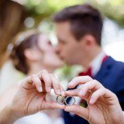 Eheringe mit küssendem Hochzeitspaar im Hintergrund