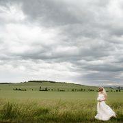 Braut steht am Feldrand, dramatische Wolken