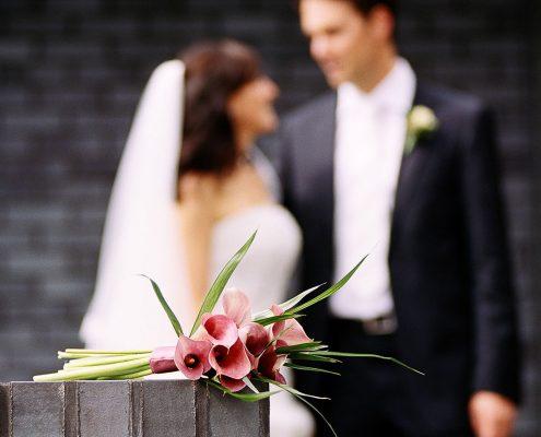 Brautstrauß mit Brautpaar unscharf im Hintergrund