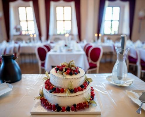 Hochzeitstorte mit festlich gedeckter Tafel im Hintergrund