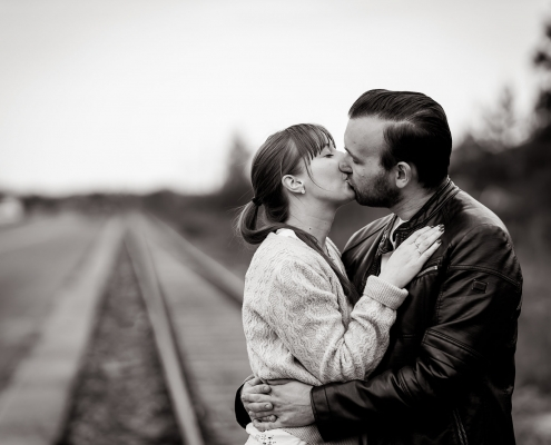 küssendes Paar auf einer Eisenbahnschiene die im Bokeh verschwindet Canon EOSR & RF 85mm f/1.2L USM